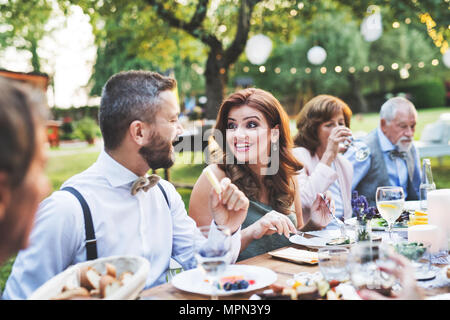 Guests eating at the wedding reception outside in the backyard. - Stock Photo
