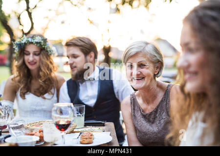 Bride and groom with guests at wedding reception outside in the backyard. - Stock Photo