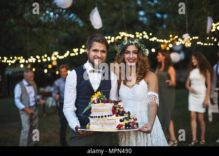 Bride and groom holding a cake at wedding reception outside in the backyard. - Stock Photo
