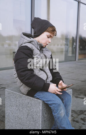 7 year old boy playing with smartphone, sitting outside in winter jacket and knit hat - Stock Photo