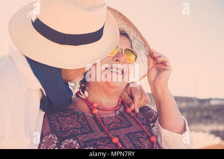 adults people stay together with kiss and hug under the sun with hats and sunglasses and necklace. true love forever together concept - Stock Photo