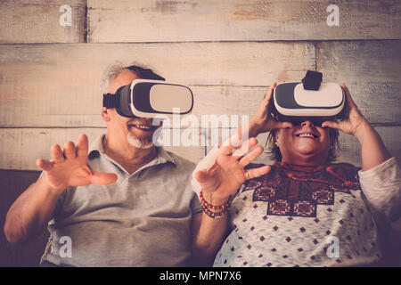seniors playing with modern vr virtual reality at home. She take the glass and he put his hands ahead to touch objects. modern concept - Stock Photo