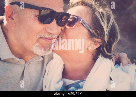 Nice love moments for two elderly woman and man kissing together with emotion. Close up scene of life to live forever. Smile and enjoy time. - Stock Photo