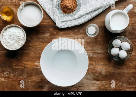 top view of ingredients for pastry and empty bowl on wooden table - Stock Photo