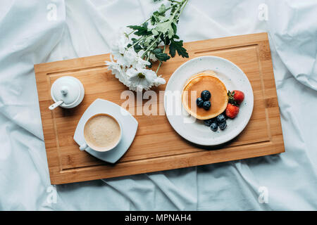 top view of breakfast in bed with delicious pancakes and coffee on wooden tray - Stock Photo