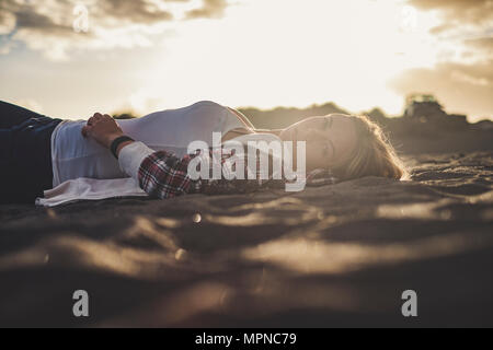 Beautiful sunset light for a cute blonde girl lay down rest on the beach in Tenerife. She look at you. Off road car parked on the background - Stock Photo