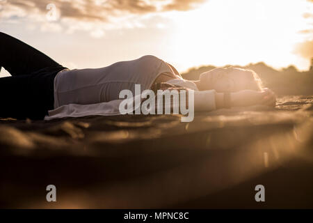 beautiful blonde woman rest on th ebeach lay down on the sand during the down sunset in tenerife. look at the camera for independent concept - Stock Photo