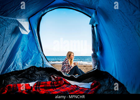 beautiful blonde woman sitting don outside the tent in free alternative vacation camping just on the beach close to the ocean. different lifestyle con - Stock Photo