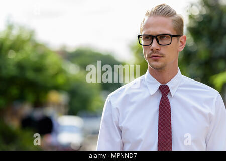 Young handsome businessman thinking while wearing eyeglasses out - Stock Photo