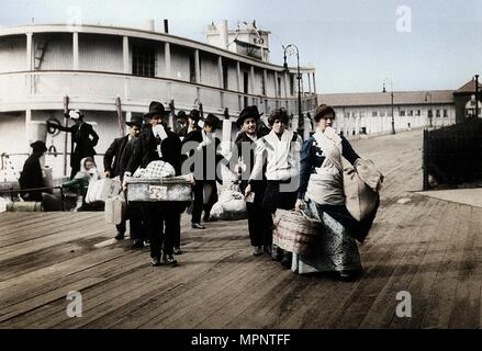 Immigrants to the USA landing at Ellis Island, New York, c1900. Artist: Unknown. - Stock Photo