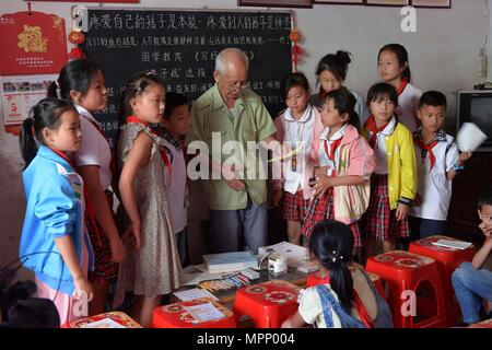 (180524) -- NANCHANG, May 24, 2018 (Xinhua) -- Miao Yanxiang awards children doing well on homework with prizes he bought at the caring station for left-behind children at his home in Shibu Town, Nanchang City of east China's Jiangxi Province, May 23, 2018. Miao, over 70, established a caring station for left-behind children at his own house in 2009, where he provided free place for children to do homework and study after school. Having received more than 3,000 children over the past nine years, Miao is satisfied with his voluntary work as he see the progress of the children. (Xinhua/Peng Zha - Stock Photo