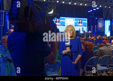 Long Island, USA. 23rd May, 2018. MARCIA KRAMER, WLNY 10/55 Political Reporter, tapes news segment with audience and stage in background during Day 1 of New York State Democratic Convention, held at Hofstra University on Long Island. Credit: Ann E Parry/Alamy Live News - Stock Photo