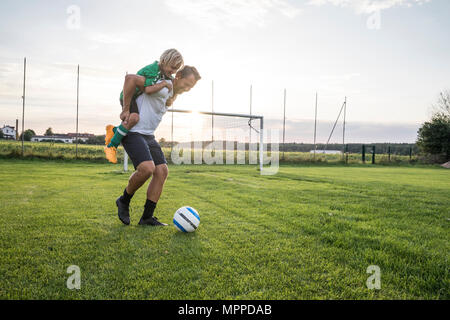 Coach carrying young football player on football ground at sunset - Stock Photo