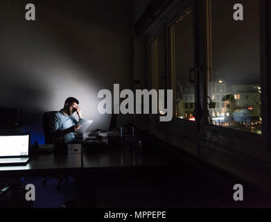 Exhausted businessman sitting at desk in his office by night - Stock Photo