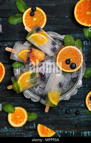 Homemade detox popsicles with blueberries, orange slices and mint leaves on black wood - Stock Photo