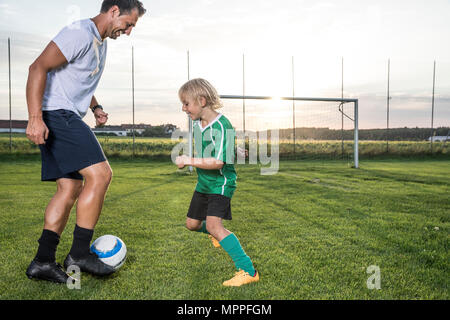 Coach and young football player on football ground at sunset - Stock Photo