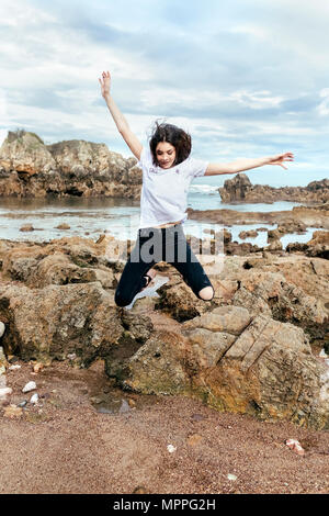 Vital brunette woman jumping on the beach - Stock Photo