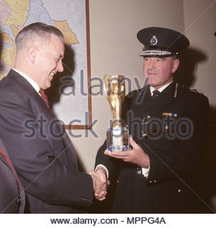 File photo dated 28/3/1966 of the recovered World Cup trophy viewed by Detective Chief Inspector William Little (left) and District Commander John Lawlor at Cannon Row police station, London. A London gangster and his brother were behind the notorious unsolved theft of the World Cup trophy just months before the 1966 tournament in England, it has been claimed. - Stock Photo