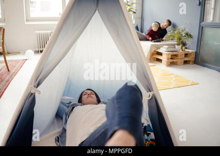 Woman resting in tent , while father is playing with their son in background - Stock Photo