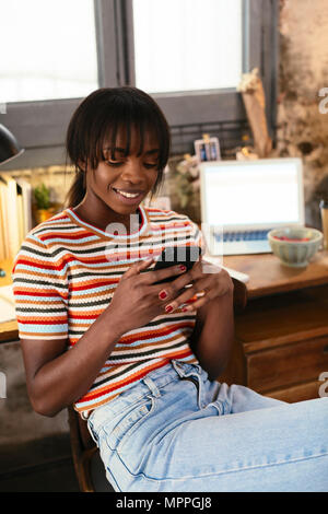 Portrait of smiling young woman sitting in front of desk in a loft using cell phone - Stock Photo