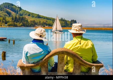 Wheeler, Oregon,USA = August 15, 2012:  A couple sitting on a bench along the shores of Tillamook Bay as a sailboat sails past in Wheeler, Oregon - Stock Photo