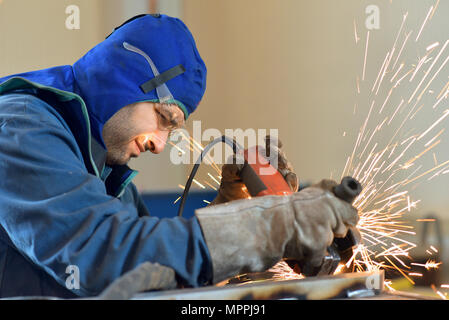 Worker using angle grinder in factory - Stock Photo