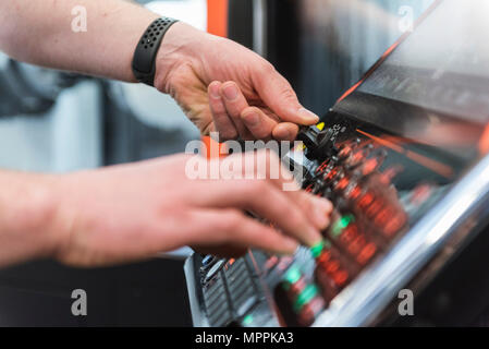 Close-up of man operating machine in factory - Stock Photo