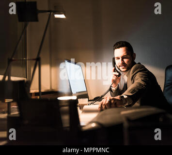 Businessman on the phone in office at night - Stock Photo