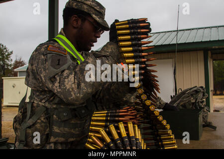 US Army Reserve Spc. Calvin Gray a motor transport operator with the 416th Theater Engineer Command and Pvt. 1st Class Donte Henderson a power generation equipment repairer with the 354th civil affairs company, 351st Civil Affairs Command prep .50 caliber machine gun ammunition to be given to the firing teams during a live fire exercise at Range 26 on Fort McCoy, Wis., for Operation Cold Steel, April 03, 2017. Operation Cold Steel is the U.S. Army Reserve's crew-served weapons qualification and validation exercise to ensure that America's Army Reserve units and Soldiers are trained and ready t - Stock Photo