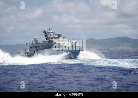 A MK VI patrol boat, assigned to Coastal Riverine Group (CRG) 1 Detachment Guam, maneuvers off the coast of Guam April 6, 2017. CRG 1 Detachment Guam is assigned to Commander, Task Force 75, which is the primary expeditionary task force responsible for the planning and execution of coastal riverine operations, explosive ordnance disposal, mobile diving and salvage, engineering and construction, and underwater construction in the U.S. 7th Fleet area of operations. (U.S. Navy Combat Camera photo by Mass Communication Specialist 3rd Class Alfred A. Coffield) - Stock Photo