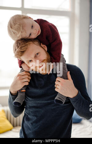 Father and baby son having fun together at home - Stock Photo