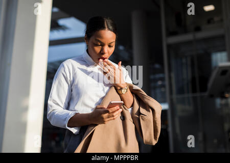 Portrait of shocked businesswoman reading email on her mobile phone - Stock Photo