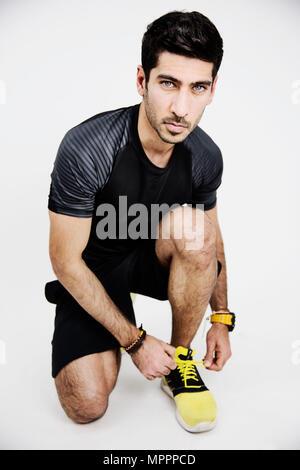 Portrait of young man wearing sportswear tying his shoe - Stock Photo