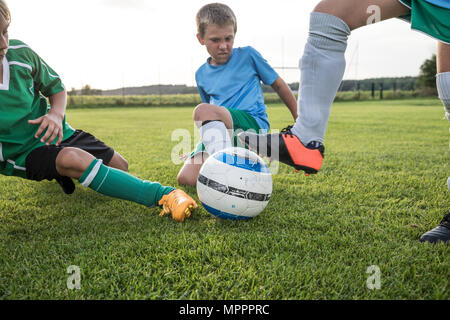 Young football players tackling on football ground - Stock Photo