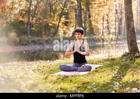 Mid adult woman in forest practicing yoga, meditation - Stock Photo