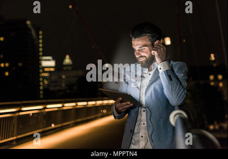 Young man on bridge at night with world map emerging from tablet - Stock Photo