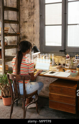 Back view of young woman sitting at desk in a loft working on laptop - Stock Photo