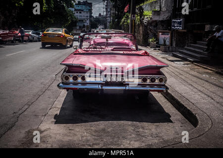 Red painted convertible Cuban classic automobile parked in calle o Havana Cuba - Stock Photo