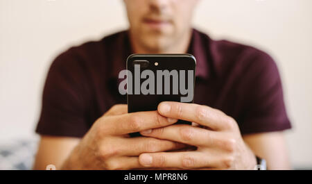 Close up of man working on mobile phone. Man operating mobile phone with two hands. - Stock Photo