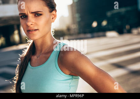 Strong woman in sports bra standing outdoors and standing at camera. Sportswoman looking with serious expressions after working out in morning outdoor - Stock Photo