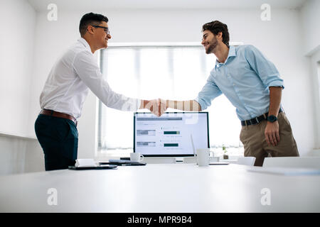 Business colleagues shaking hands in the conference table. Happy businessmen greeting each other in the meeting room. - Stock Photo