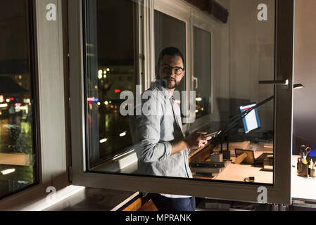 Portrait of businessman working late in office - Stock Photo