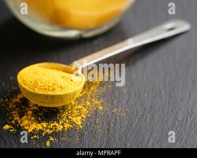 Close-up of measuring spoon full of curcuma - Stock Photo