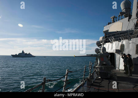 170410-N-ZE250-055      PLYMOUTH, United Kingdom - (April 10, 2017) - Sailors aboard USS Carney (DDG 64) render honors to the Royal Netherlands Navy frigate HNLMS De Ruyter (F804) while departing Plymouth, United Kingdom April 10, 2017. Carney, an Arleigh Burke-class guided-missile destroyer, forward-deployed to Rota, Spain, is conducting its third patrol in the U.S. 6th Fleet area of operations in support of U.S. national security interests in Europe. (U.S. Navy photo by Mass Communication Specialist 3rd Class Weston Jones/Released) - Stock Photo