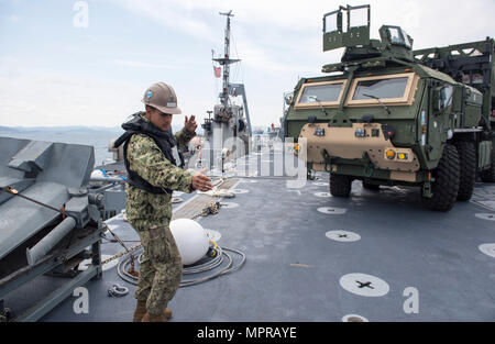 170410-N-OU129-133 POHANG, Republic of Korea (Apr. 10, 2017) Equipment Operator 3rd Class Richard Engelhard directs the offloading of equipment from Navy Maritime Prepositioning Force Ship USNS Pililaau (T-AK 304), utilizing a roll-on, roll-off discharge facility (RRDF) while anchored off the coast of Pohang, Republic of Korea during Combined Joint Logistics Over the Shore (CJLOTS) April 10. CJLOTS is a biennial exercise conducted by military and civilian personnel from the United States and the Republic of Korea, training to deliver and redeploy military cargo as a part of exercise Foal Eagle - Stock Photo