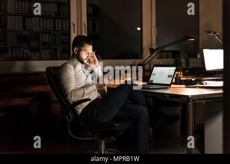 Businessman using tablet in office at night - Stock Photo