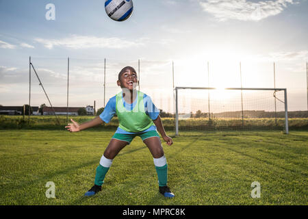 Young football player heading the ball on football ground - Stock Photo