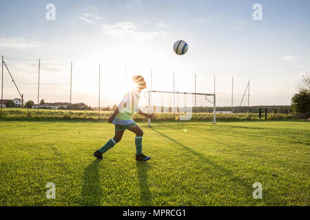 Young football player heading the ball on football ground at sunset - Stock Photo