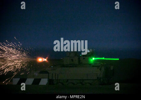 An M2A3 Bradley Fighting Vehicle crew from the 3rd Armored Brigade Combat Team, 1st Cavalry Division shoots at target during the night fire portion of Table VI qualifications at the Udairi Range Complex March 29. The brigade tank and Bradley crews spent about two weeks in the field conducting sustainment gunnery to ensure all the crews qualified at day and night fire to maintain proficiency. (U.S. Army photo by Staff Sgt. Leah R. Kilpatrick, 3rd Armored Brigade Combat Team Public Affairs Office, 1st Cavalry Division (released) - Stock Photo