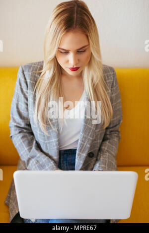 Businesswoman sitting on yellow couch, using laptop - Stock Photo
